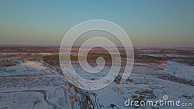 Schneebedeckte Felder bei Sonnenuntergang aus Vogelperspektive stock footage
