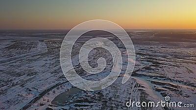 Schneebedeckte Felder bei Sonnenuntergang aus Vogelperspektive stock video