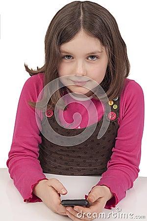 Schönes kleines Mädchen, das mit einem Handy spielt