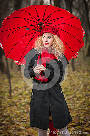 Schönes modernes junges Mädchen mit rotem Regenschirm, roter Kappe und rotem Schal im Park