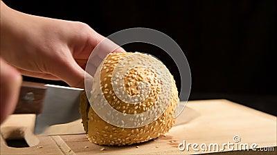 Schnitt des Brötchens mit Samen des indischen Sesams mit einem Küchenmesser auf hölzernem stock video
