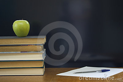 School books with green apple on desk.