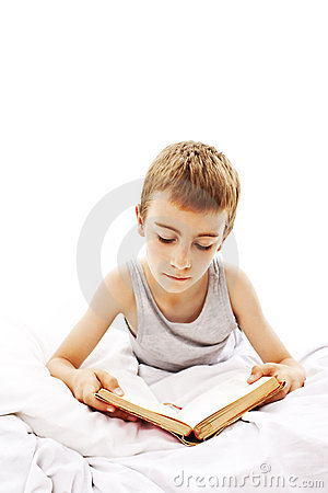 School boy reading a book on his bed.