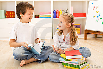 School boy showing her little sister how to read