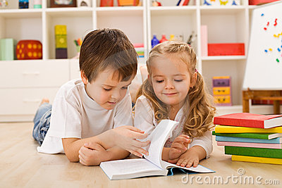 School boy teaching her sister how to read