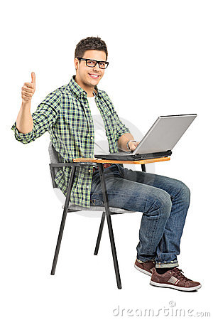School boy working on a laptop and giving thumb up