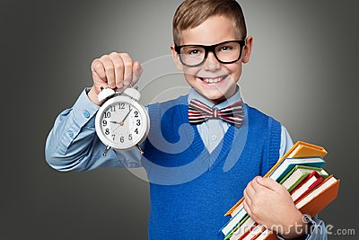 School Child in Glasses with Alarm Clock and Books, Smart Kid Stock Photo