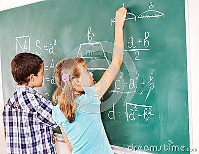 School child writting on blackboard.