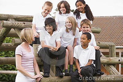 School children sitting on benches outside
