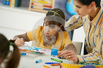School children and teacher in art class