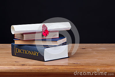 School desk with dictionary black background