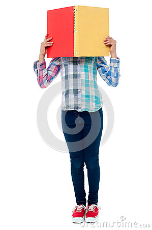 School girl hiding her face behind a notebook