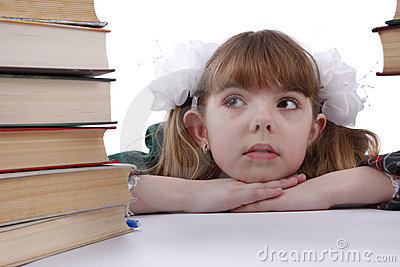 School girl is looking at the heap of books.