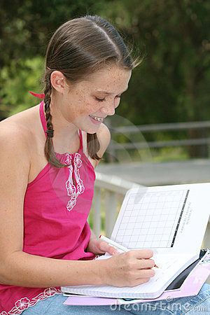 School Girl writing in Notebook Outdoors