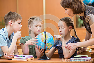 School kids studying a globe
