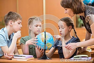 School kids studying a globe