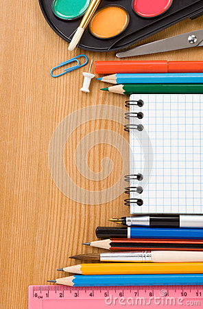 School supplies and checked notebook on wood