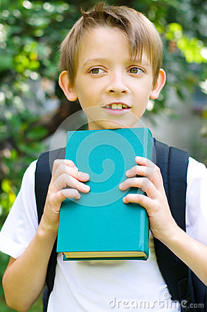 Schoolboy with backpack and book