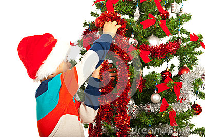 Schoolboy decorate Christmas tree