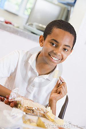 Schoolboy enjoying his lunch in a school cafeteria