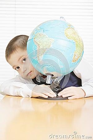 Schoolboy hiding behind globe