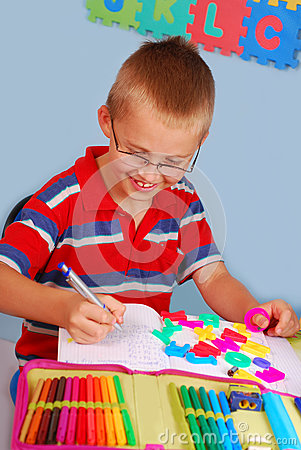 Schoolboy learning to write letters