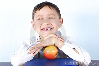 Schoolboy without several tooth s with apple