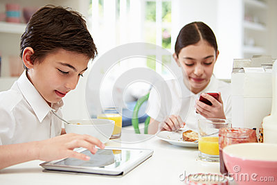 Schoolchildren With Digital Tablet And Mobile At Breakfast
