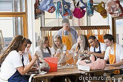 Schoolchildren and teacher sitting around a table