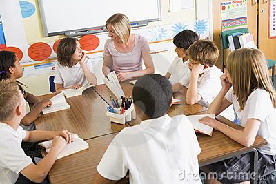 Schoolchildren and their teacher reading in class