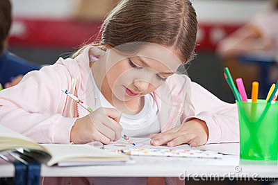 Schoolgirl Drawing At Desk