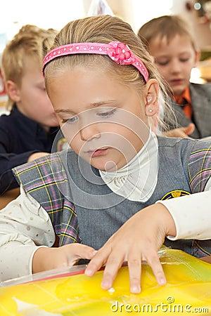 Schoolgirl with a folder in classroom