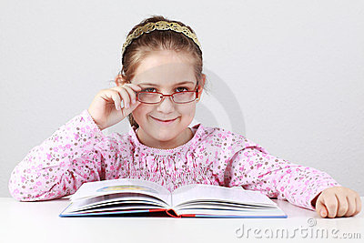Schoolgirl with glasses reading book