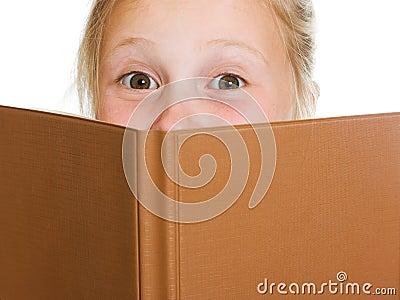 Schoolgirl is hiding behind a book