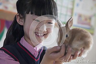 Schoolgirl holding pet rabbit in classroom