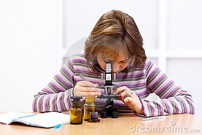 Schoolgirl looking into microscope