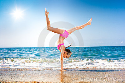 Schoolgirl making gymnastics on seashore or beach