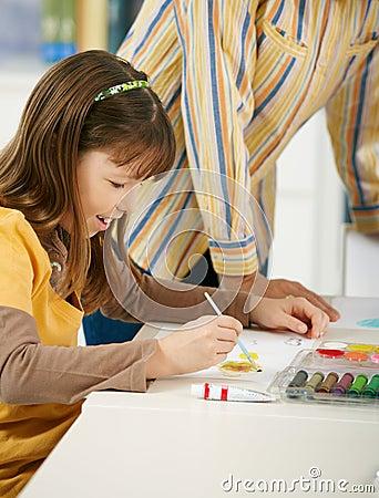 Schoolgirl painting in art class