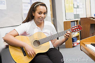 Schoolgirl playing guitar in music class