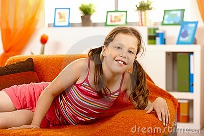 Schoolgirl posing on sofa at home