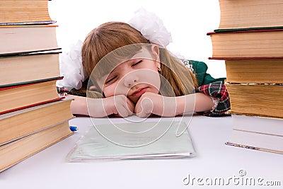 Schoolgirl is sleeping near her homework.