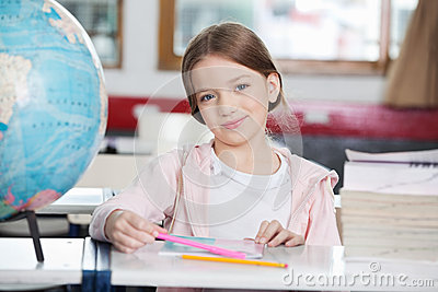 Schoolgirl Smiling With Books And Globe At Desk