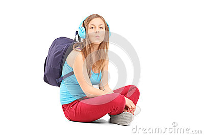 A schoolgirl with speakerphones sitting on a floor and giving ki