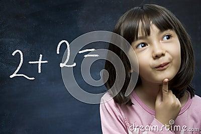 Schoolgirl stay near school blackboard.