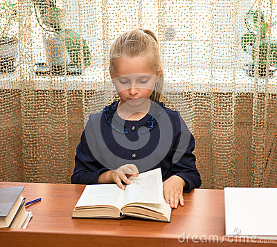 Schoolgirl studying and reading book at school