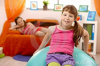 Schoolgirls at home, with gym ball