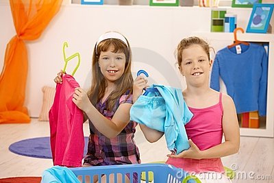 Schoolgirls sorting clothes at home