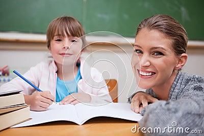 Schoolmeisje dat met haar leraar schrijft