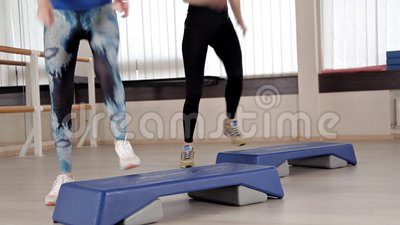 Schrittplattformen M?dchen in den Sportschuhen, die ?bungen f?r Aerobic tun Das Konzept des Festziehens in die Turnhalle f?r Gewi stock video