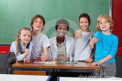 Schulkinder, die oben Daumen gestikulieren